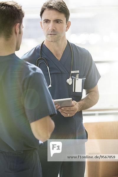 Zwei männliche Ärzte reden  einer hält die Tablette.