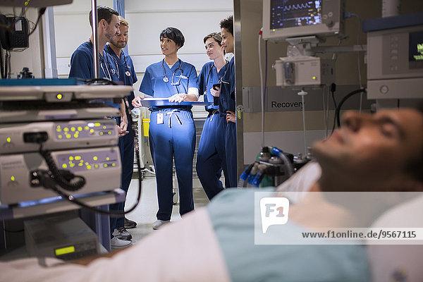 Patient an medizinische Überwachungsgeräte auf der Intensivstation angeschlossen  Ärzte im Eingangsbereich stehend