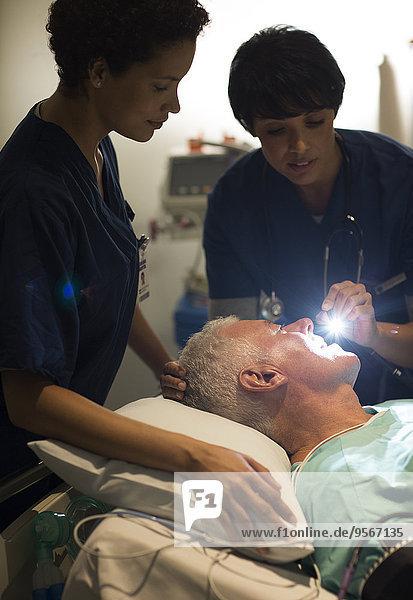 Ärztin untersucht ältere Patientin mit Taschenlampe auf der Intensivstation