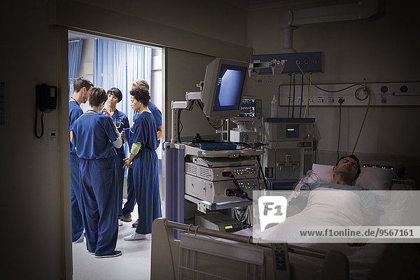 Patient liegt im Bett auf der Intensivstation  Ärzteteam diskutiert im Hintergrund