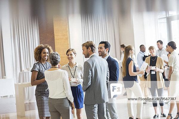 Gruppe von Geschäftsleuten  die in der Halle stehen  lächeln und miteinander reden.