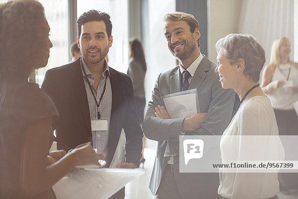 Gruppe von Geschäftsleuten lächelnd und diskutierend im Büro