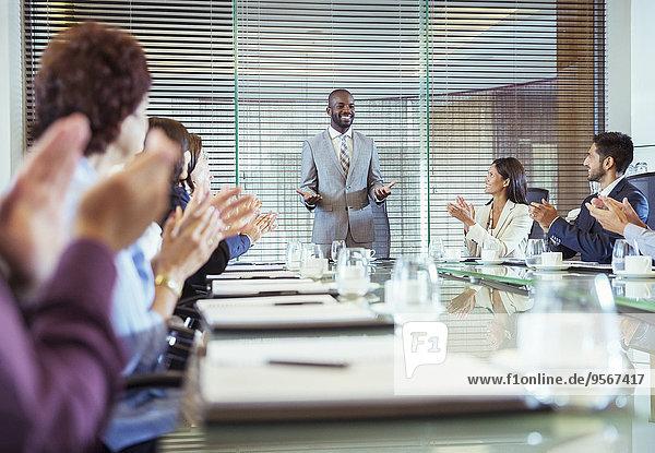 Geschäftsmann steht im Konferenzraum und hält eine Rede  Kollegen klatschen in die Hände.