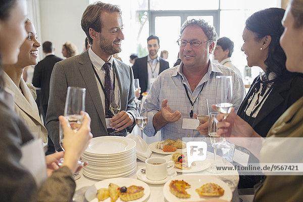 Geschäftsleute stehen am Tisch im Büro  reden und trinken Champagner.