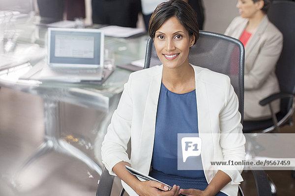 Porträt einer lächelnden Geschäftsfrau mit Tablet PC im Konferenzraum