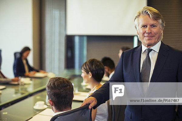 Portrait des Geschäftsmannes im Konferenzraum mit Kollegen im Hintergrund