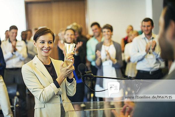 Unternehmerin verleiht Auszeichnung an Unternehmer  Kollegen im Hintergrund