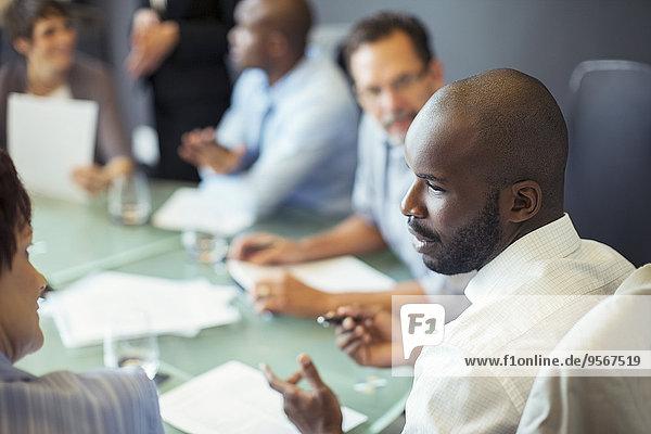 Geschäftsmann im Gespräch mit Kollegen während der Geschäftsbesprechung im Konferenzraum
