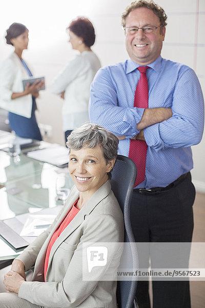 Zwei reife Geschäftsleute mit Blick auf die Kamera  lächelnd im Konferenzraum