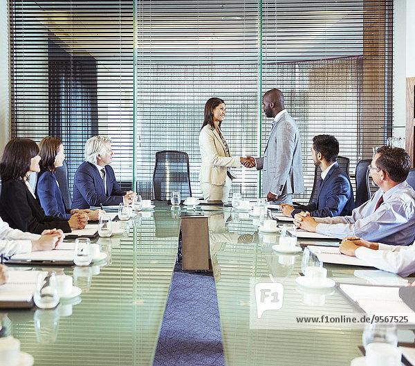 Geschäftsleute schütteln sich im Konferenzraum während eines Geschäftstreffens die Hand.