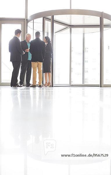 Geschäftsleute stehen und reden vor der Haustür des Büros