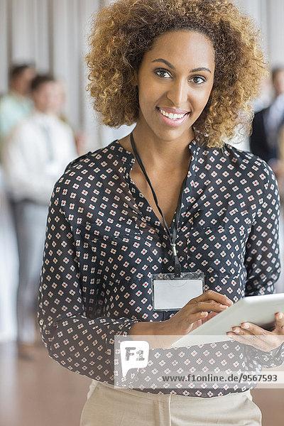 Porträt einer schönen Frau mit braunem Lockenhaar  die ein digitales Tablett hält.