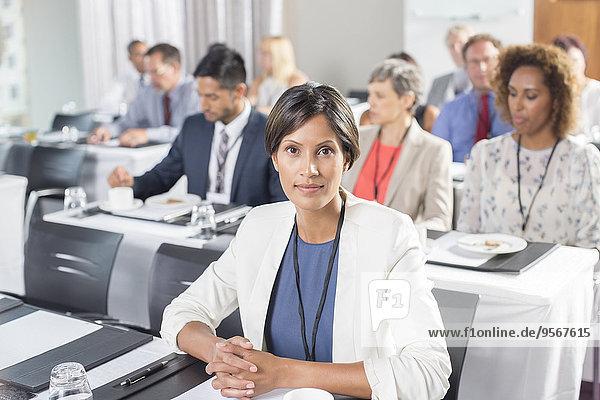 Porträt einer Frau mit einer Gruppe von Geschäftsleuten im Hintergrund beim Seminar