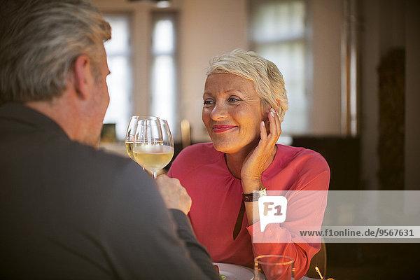 Ältere Paare stoßen sich gegenseitig mit Weißwein an.