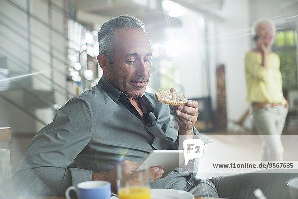 Älterer Mann mit digitalem Tablett am Frühstückstisch
