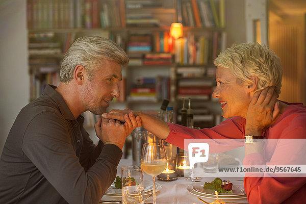 Älterer Mann küsst Hand der Frau beim romantischen Abendessen