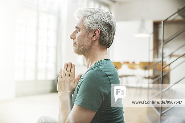 Älterer Mann beim Meditieren im Haus