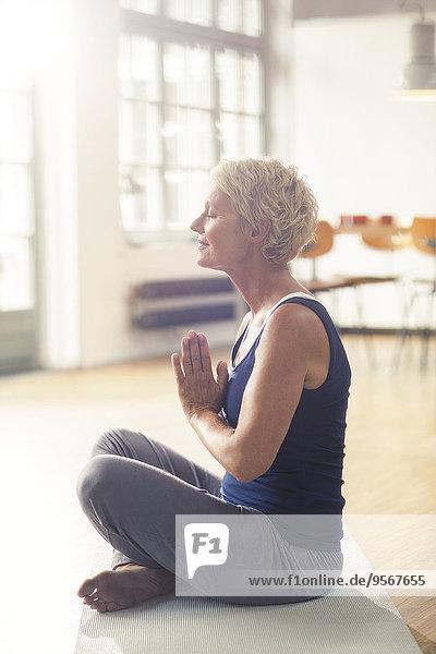 Ältere Frau meditiert auf Trainingsmatte