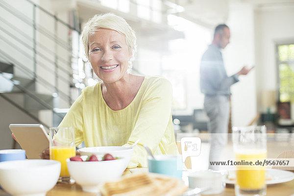 Ältere Frau mit digitalem Tablett am Frühstückstisch