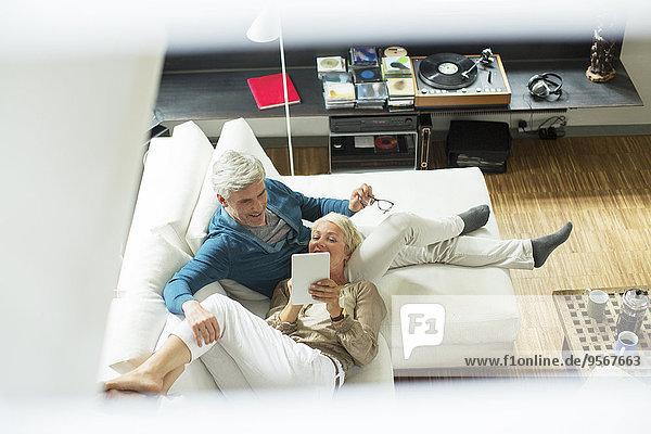 Hochwinkelansicht des älteren Paares mit digitalem Tablett auf dem Sofa