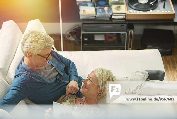 Hoher Blickwinkel auf ein älteres Paar  das sich gemeinsam auf dem Wohnzimmersofa ausruht