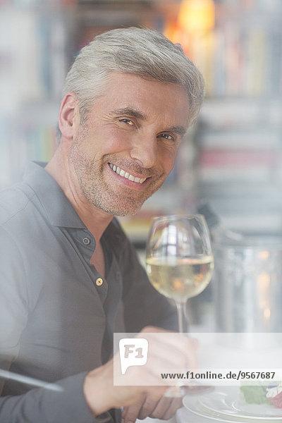 Älterer Mann trinkt Weißwein beim Abendessen
