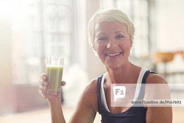 Lächelnde ältere Frau trinkt Saft