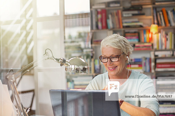 Geschäftsfrau  die Ohrhörer hört und im Home-Office arbeitet