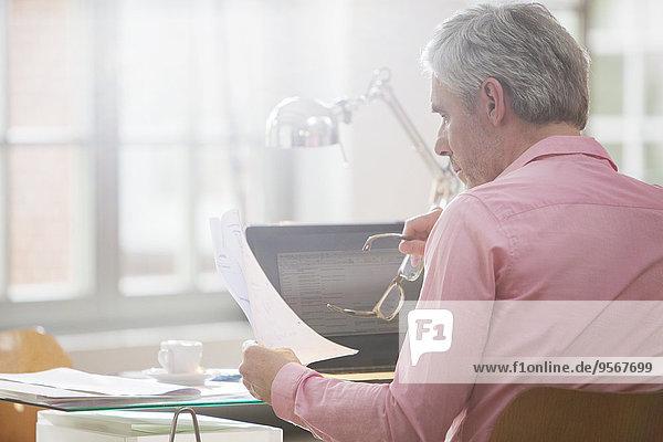 Geschäftsmann beim Lesen von Papierkram am Schreibtisch zu Hause