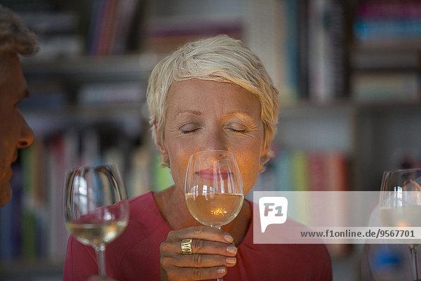 Ältere Frau riecht Weißwein