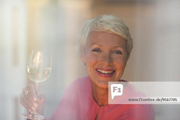 Ältere Frau trinkt ein Glas Weißwein