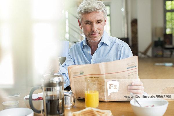 Älterer Mann liest Zeitung am Frühstückstisch