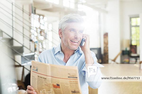 Älterer Mann im Gespräch am Handy mit Zeitung