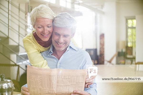 Ältere Frau umarmt Mann beim Zeitungslesen