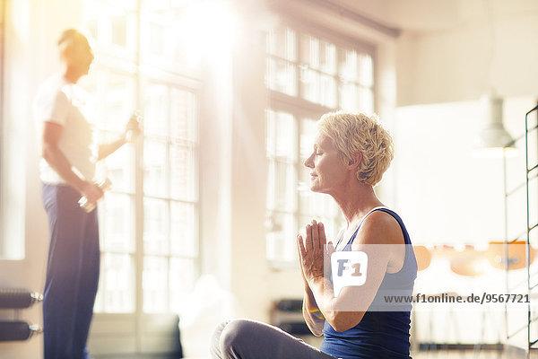 Ältere Frau meditiert auf dem Boden