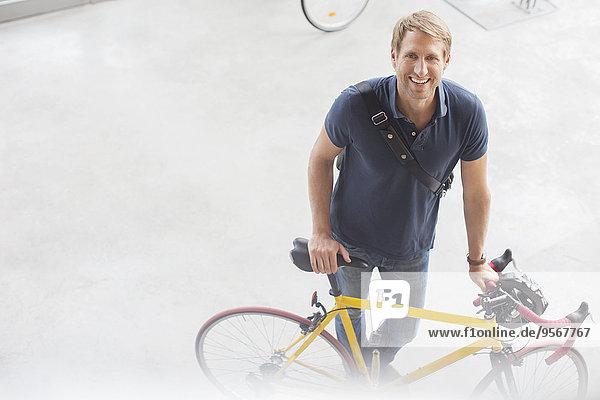 Lächelnder Mann stehend mit Fahrrad