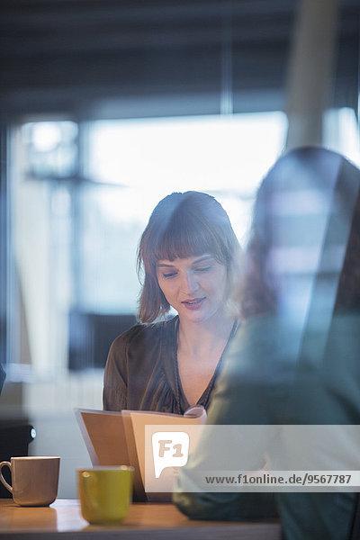 Geschäftsfrauen lesen Papierkram im Büro