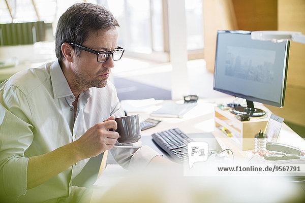 Geschäftsmann trinkt eine Tasse Kaffee am Bürotisch