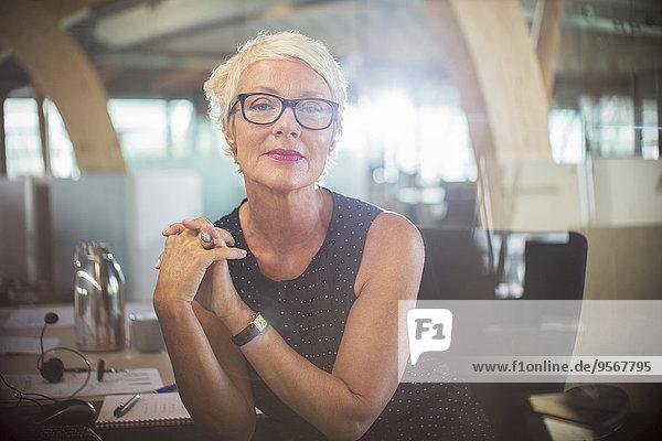Geschäftsfrau sitzend mit gefesselten Händen am Schreibtisch