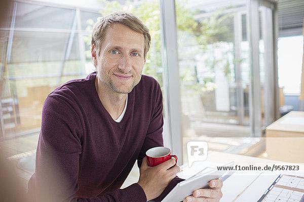 Geschäftsmann mit digitalem Tablett am Schreibtisch