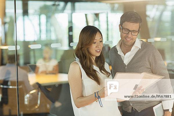 Geschäftsleute lesen Papierkram im Büro