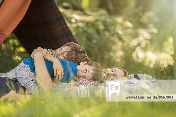 Father and sons relaxing together near camping tent