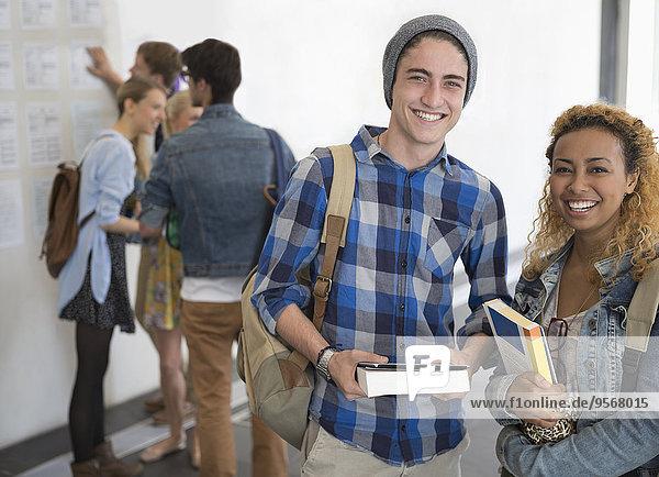 Porträt zweier lächelnder Universitätsstudenten im Flur