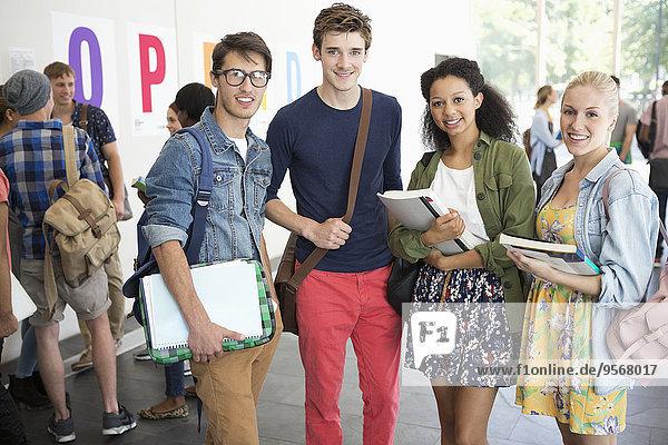 Porträt von lächelnden Universitätsstudenten  die neben der Universität stehen