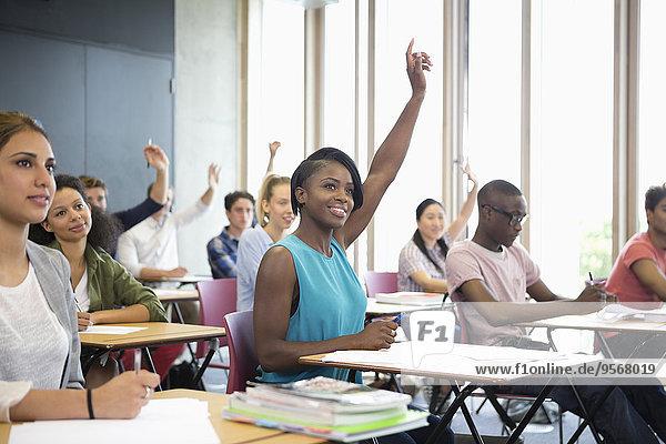 Motivierte Universitätsstudenten heben die Hand beim Seminar