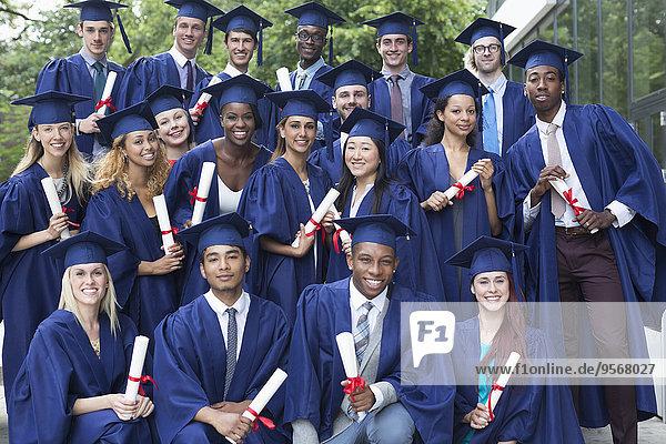 Portrait von Universitätsstudenten in Promotionskleidern im Freien