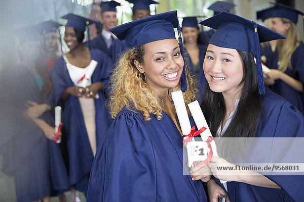 Porträt von lächelnden Studenten mit Diplomen auf dem Flur