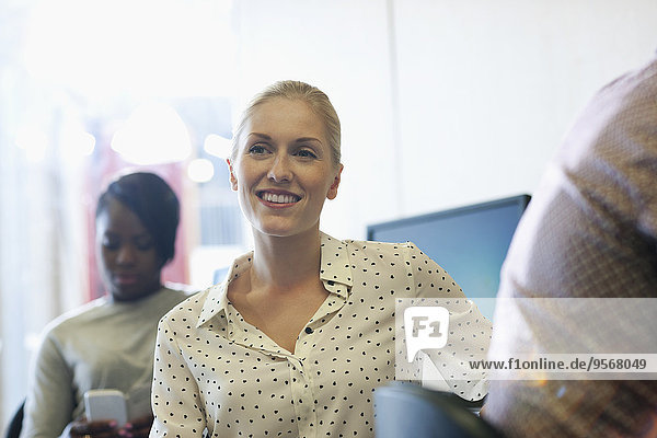 Smiling university student listening to seminar  young woman texting in background
