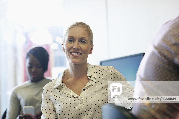 Lächelnde Studentin beim Seminar  junge Frau beim SMSen im Hintergrund