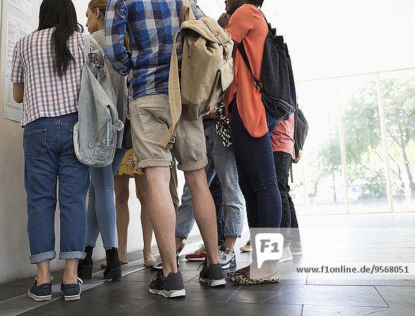Niederwinkelansicht der Studenten  die im Flur stehen und die Testergebnisse betrachten.